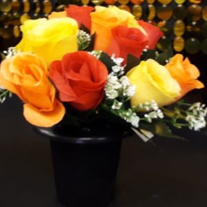 A Black Plastic Grave Pot with Yellow, Orange and Red Rosebuds and Gyp